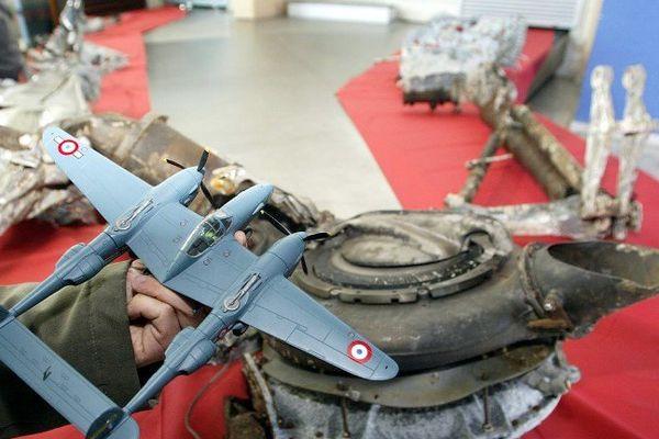 Une personne présente une maquette de l'avion Lightning P38, le 09 avril 2004 à la base aérienne d'Istres, devant les fragments d'un train d'atterrissage de l'avion d'Antoine de Saint-Exupéry.