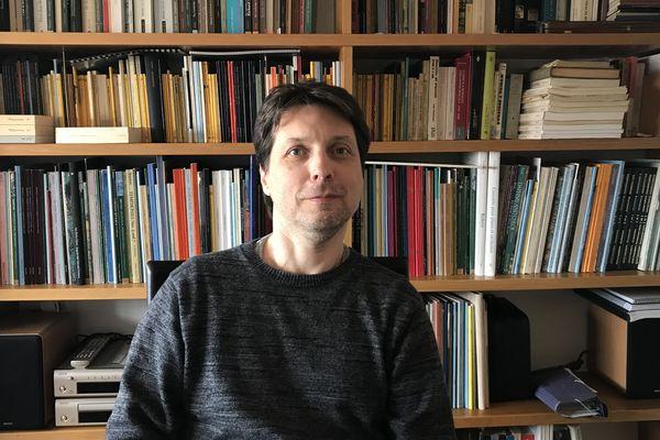 Roberto Forés Veses, le chef de l'Orchestre national d'Auvergne devant sa bibliothèque, un élément très important de son confinement chez lui à Valence en Espagne.