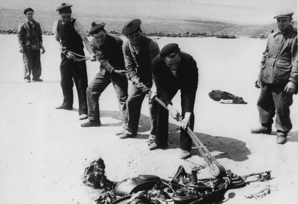 Des prisonniers de guerre français nettoyant une plage de Dunkerque en juillet 1940. Ici visiblement une moto ensablée, vestige de l'Opération Dynamo et de l'évacuation des troupes britanniques en mai/juin 1940.