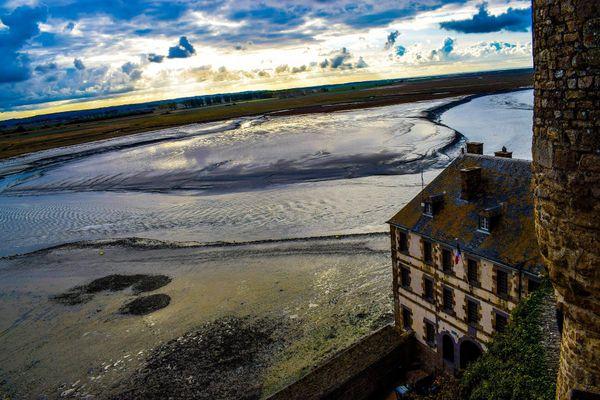 Entre sable, reflets et nuages, la lumière unique du spectacle des grands marées, vues du Mont Saint Michel.