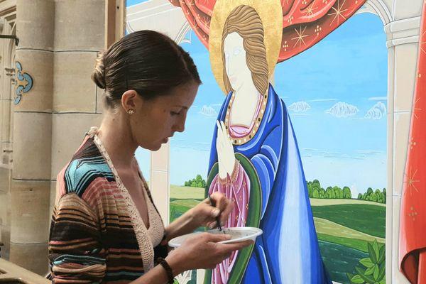L'artiste Florence Aseult en train de peindre l'un des deux volets destinés à l'orgue de Notre-Dame de l'Epine. Celui-ci représente la Vierge Marie dans un décor rappelant les paysages marnais.