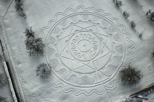 Vue d'un mandala dessiné dans la neige dans un champs de Minversheim par Patrick Straub.
