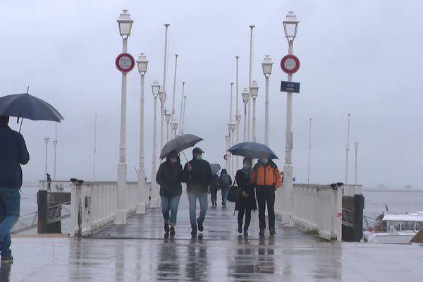 Malgré la pluie, les promeneurs tentent de profiter d'un bol d'air marin à Arcachon.