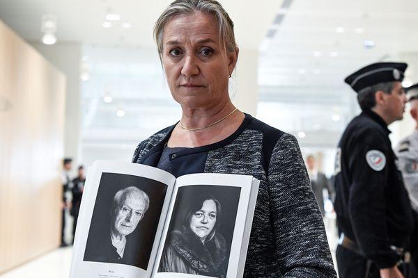 La Dr Irène Frachon tient des portraits de victimes lors de son arrivée au tribunal, le 23 septembre.