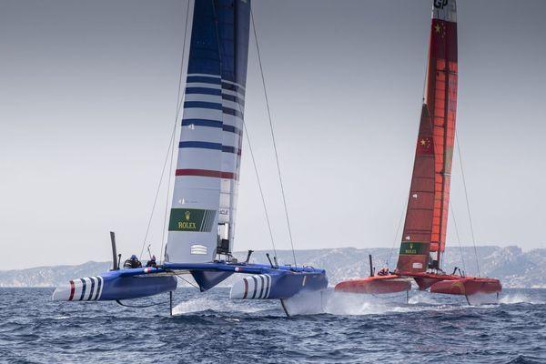 Le F50 de l'équipe de France vole au-dessus de l'eau. Ici à l'entraînement avec leur concurrent direct, la Chine