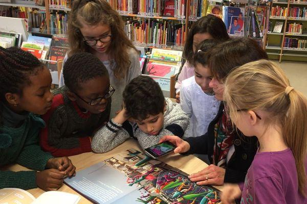 Des enfants lisant un livre avec réalité augmentée