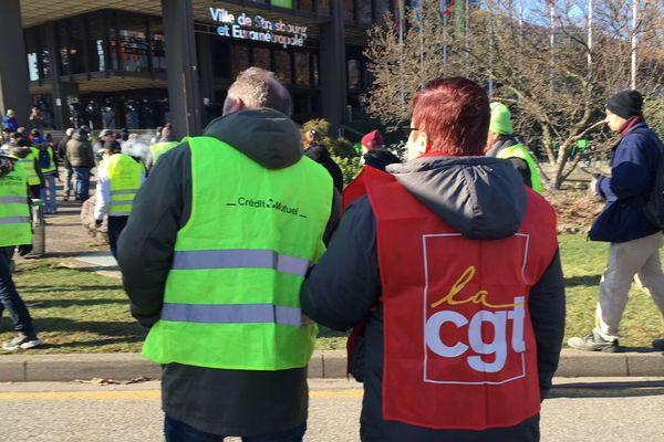 Gilets jaunes et rouges main dans la main devant le centre administratif de Strasbourg.