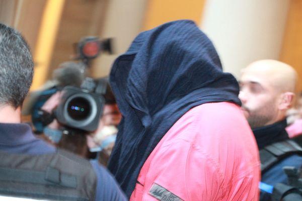 Le principal suspect de l'affaire Sophie Le Tan, Jean-Marc Reiser, ici avec le visage recouvert d'un drap, à la sortie de l'audience de sa première demande de remise en liberté, devant la chambre de l'instruction à la cour d'appel de Colmar