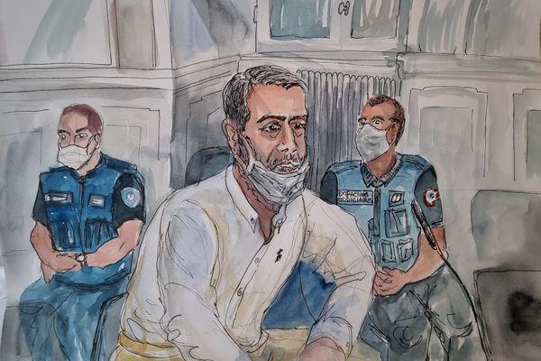 Dans son box d'accusé, Nordahl Lelandais entouré de deux policiers.