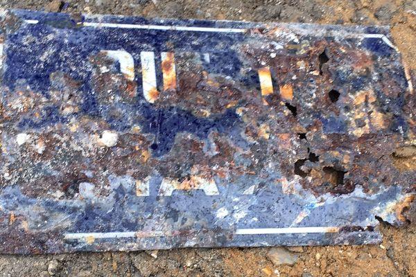 Les vestiges de la plaque de la rue au Change dévorée par le feu le 9 juin 1940