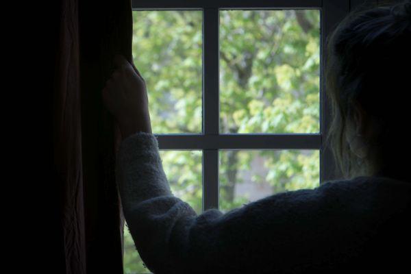 Une femme regarde par la fenêtre, pendant le confinement - Photo d'illustration