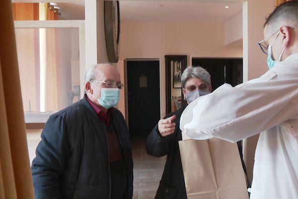 Richard Rocles de l'Auberge de Montfleury remet les plats à emporter à Gisèle et Jean-Pierre ce samedi 12 décembre