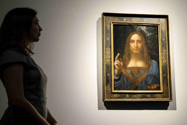 Une employée de Christie's pose devant la peinture Salvator Mundi de Léonard de Vinci at a photocall, à la vente aux enchères Christie's de Londres, le 22 octobre 2017, avant la vente de New York programmée le 15 novembre