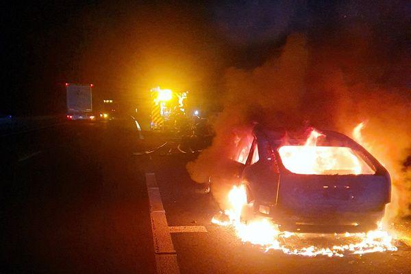 Le véhicule en feu sur le bord de l'autoroute