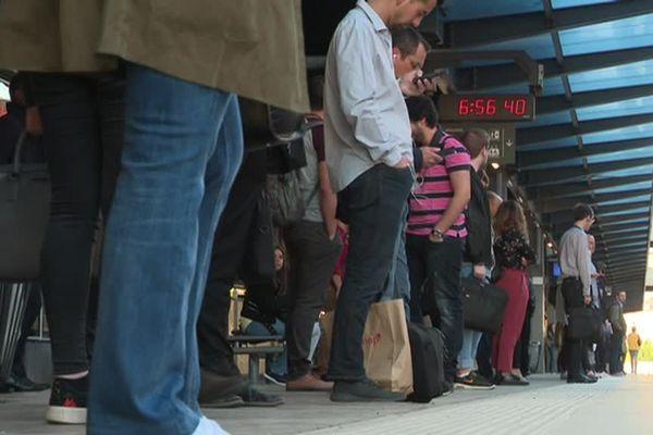 Sur le quai de gare, les voyageurs attendent le TER pour Luxembourg.