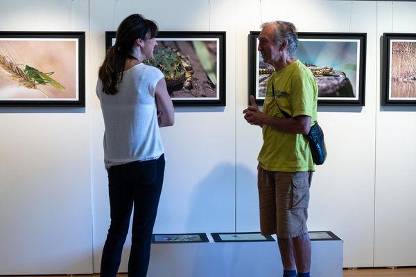 Le photographe aime faire la visite de l'exposition au public.