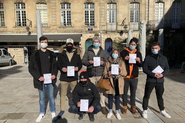 """Au nom des """"Restaurateurs debout"""", ils montrent un tract des métiers liés à la restauration et fragilisés par la crise sanitaire. Bordeaux Janvier 2021 -"""