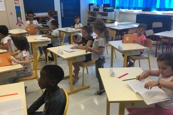 Plusieurs élèves assis à leur table dans leur classe.
