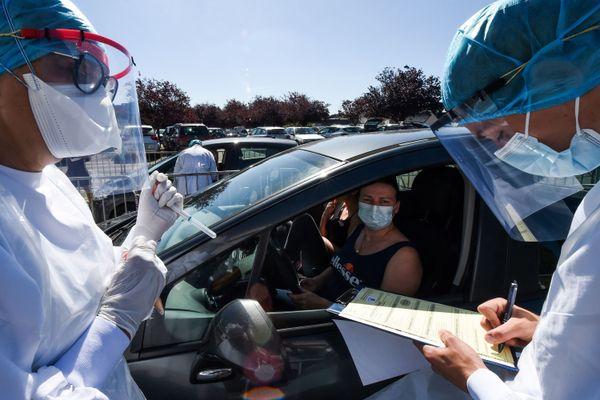 """Sur le parking """"Covid"""" de l'hôpital de Laval en Mayenne, le personnel se prépare a effectuer des prélèvement sur les membres d'une famille"""