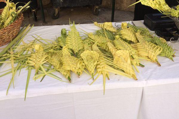 Des rameaux de feuilles de palmes tressées.