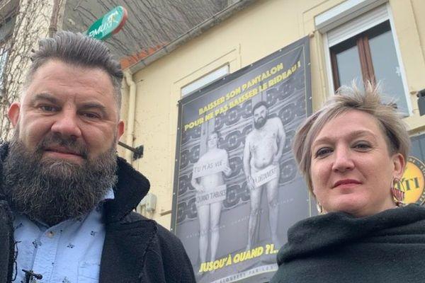 Derrière Yann Malet et son épouse Mathilde, une affiche les présentant nus, accrochée sur la façade de leur café à Outreau