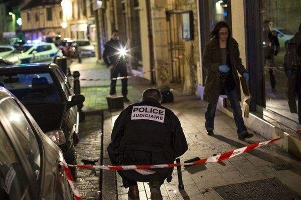 """A Dijon, un policier collecte des preuves sur le lieu d'un des accidents causés par un homme qui a volontairement blessé 13 passants en criant """"Allahou Akbar"""" (Allah est grand) lundi 22 décembre 2014."""