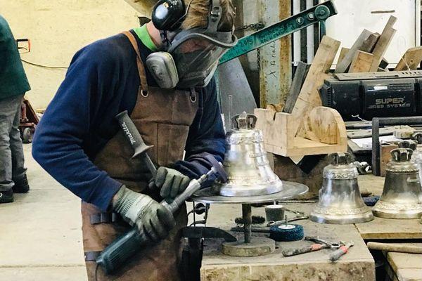 Un artisan campanaire en train de travailler sur un cloche.