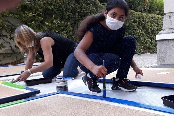 Zaïneb,, 11 ans, rafraîchit les couleurs de cadres d'exposition