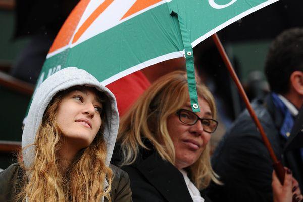 Des spectateurs à Roland-Garros, sous un parapluie.