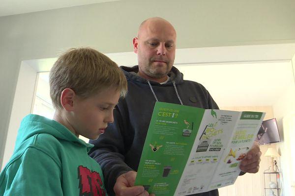 La famille Boissonnot s'est portée volontaire pour trier les biodéchets. Yohann et son fils consulte le mode d'emploi du tri des biodéchets.