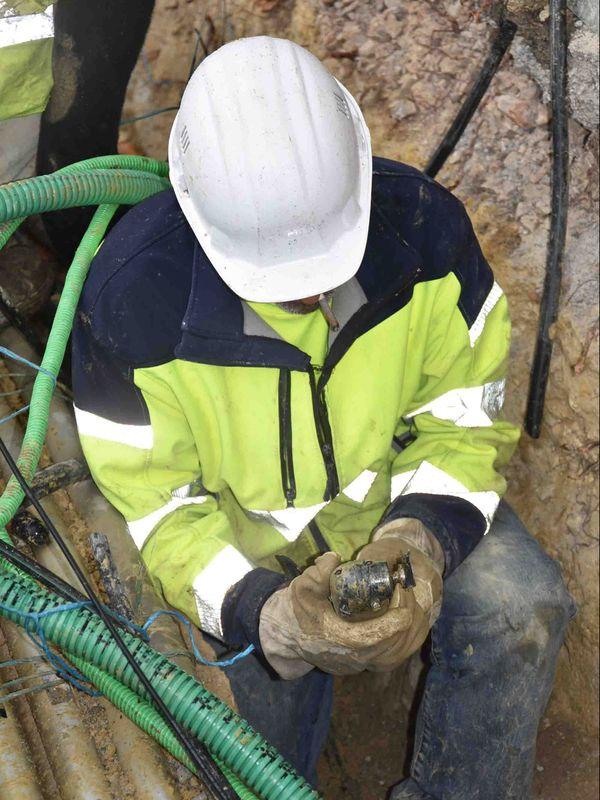 Technicien d'Orange travaillant sur un câble de fibre optique