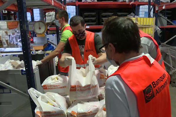 Dans le hangar de la banque alimentaire de Bordeaux, les bénévoles, gilets orange s'activent pour la distribution d'été