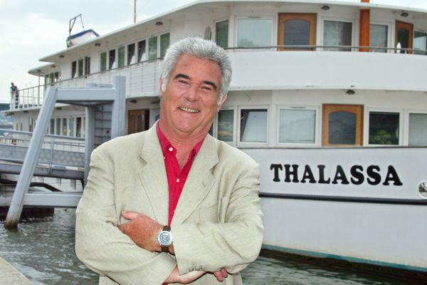 Georges Pernoud pose, le 16 juin 2004, quai de Javel à Paris, devant le bateau de l'émission de France3 Thalassa.