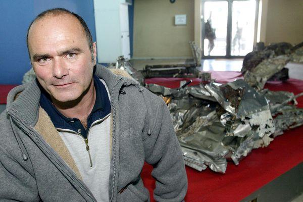Luc Vanrell en 2004 devant les débris de l'avion d'Antoine de Saint-Exupéry à la base aérienne d'Istres.