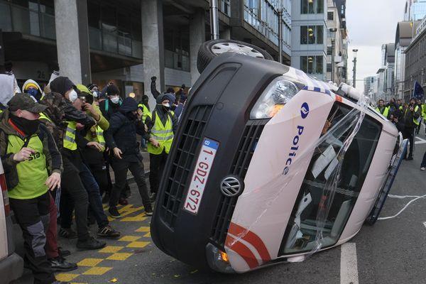 Des manifestants en gilets jaunes renversant un véhicule de police à Bruxelles.