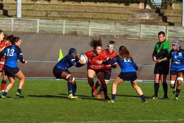Le ballon en main, Caroline Drouin (au centre) aux prises avec ses adversaires lors d'un match du Stade rennais rugby contre le Montpellier rugby club Hérault