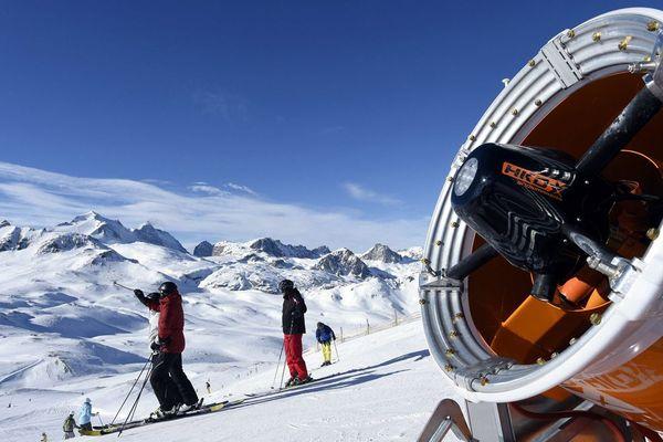 Des skieurs et un canon à neige sur le domaine skiable de Bellevarde à Val d'Isère.