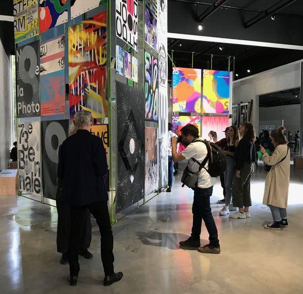 Les visiteurs découvrent avec plaisir et curiosité les affiches du concours international.