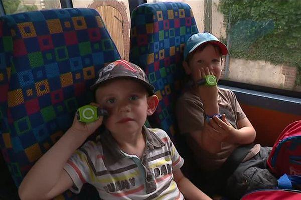 Dans le bus, les enfants sont fiers de montrer leurs bracelets connectés.
