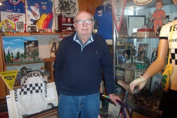 Claude devant ses vitrines : une passion sans frein pour le cyclisme!