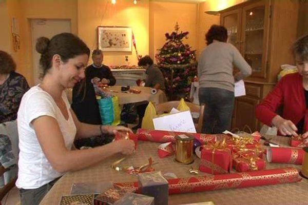Julie et Christine, bénévoles des Petits frères des pauvres emballent des cadeaux à destination d'une maison de retraite.