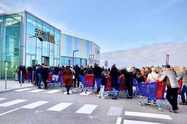 Dans le calme, une file d'attente de consommateurs avant midi devant un supermarché de Boisseuil