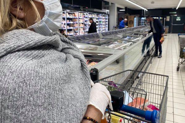Marie a pris ses précautions avant de faire ses courses : un masque et des gants.