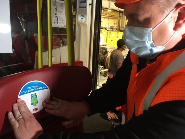 Un agent de la SNCF en train de poser un autocollant sur un siège d'un TER