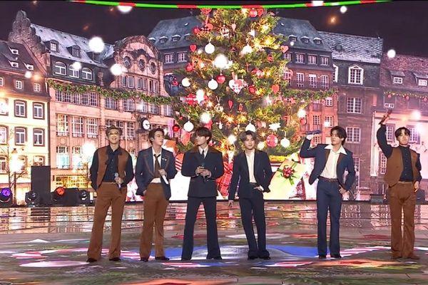 Performance finale des BTS lors du KBS Song Festival, avec la place Kléber aux couleurs de Noël reconstituée derrière eux.