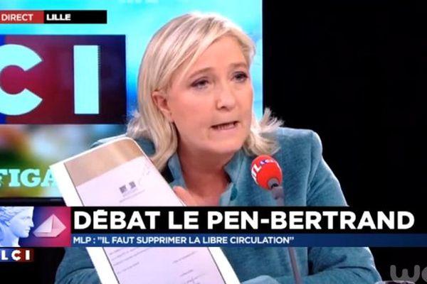 """Marine Le Pen brandit un laissez-passer délivré par la sous-préfecture du Pas-de-Calais aux habitants du chemin des dunes à Calais, riverains de la """"Jungle"""""""