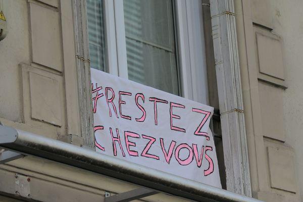 """Un écriteau """" Restez chez vous """" posé sur une fenêtre à Paris."""