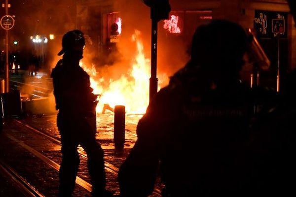 Un policer devant un départ de feu à Bordeaux, lors de la 10e journée de mobilisation des Gilets jaunes