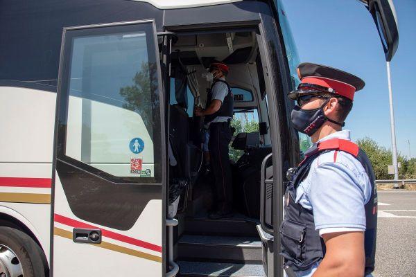Des policiers espagnols contrôlent un bus sur la route qui mène aux plages à Torregrossa, en Catalogne, le 5 juillet 2020