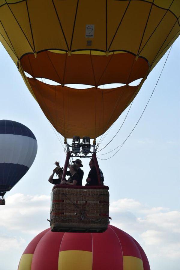 Un pilote et ses passagers à bord d'une montgolfière. Édition 2019 du Grand Est Mondial Air Ballons.